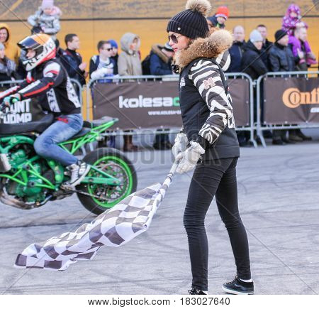 St. Petersburg Russia - 15 April, Girl with checkered finish flag,15 April, 2017. International Motor Show IMIS-2017 in Expoforurum. Sports motorcycle show of bikers on the open area.