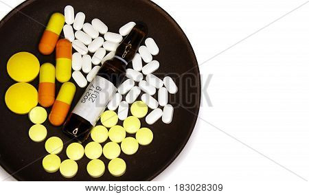 Yellow and white pills yellow capsules and brown ampoule with medicine on a brown plate isolated