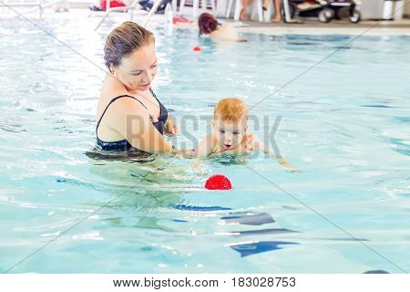 Adorable Baby Girl Enjoying Swimming In A Pool With Her Mother, Early Development Class For Infants