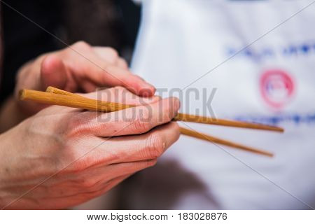 Hand holding chopsticks ready to tasty eat.