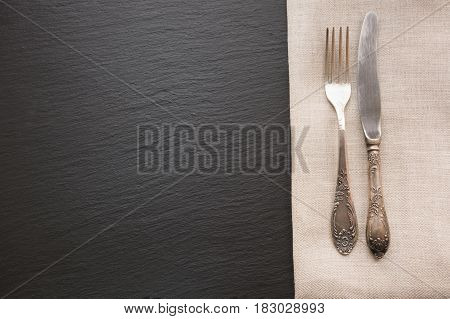 Rustic linen napkin, silverware and black slate dish with copy space for your menu or recipe. Menu card for restaurants.