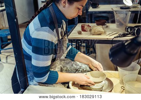 Young woman potter works with clay making ceramic handmade crockery in pottery workshop or studio