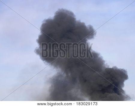 pillar of black smoke due to illegal burning of waste