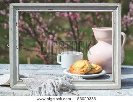 White frame, porcelain pink jug, cup and bakery on a table of white boards against the background of flowering bush