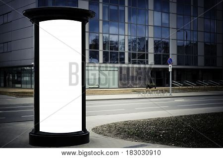 Advertising column mockup. Blank public information board mock up in front of the modern architecture building with glass windows
