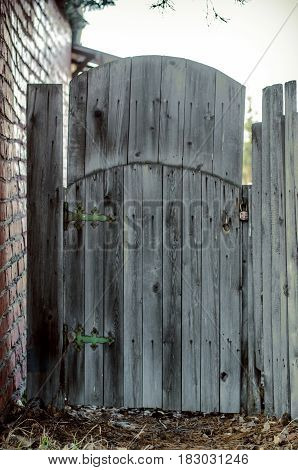 Old wooden wicket gate in countryside yard.