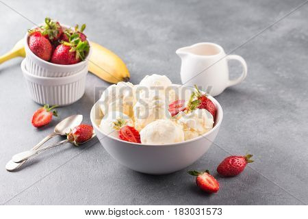 Homemade vanilla ice cream with strawberry in bowl. Maple syrup.