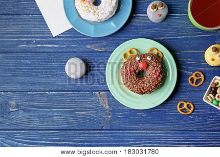 Plates with creative donuts on wooden background