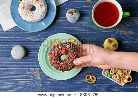 Female hand holding creative donut on wooden background