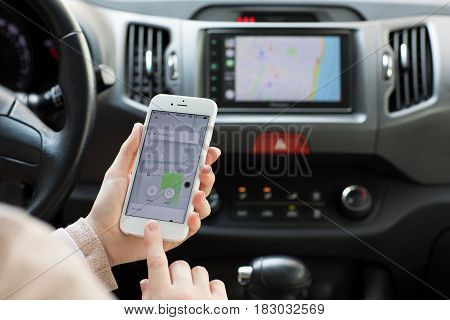 Alushta Russia - April 18 2017: Woman hands holding iPhone 6 S with application Taxi Uber in the screen. iPhone was created and developed by the Apple inc.