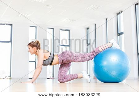 Young woman training with fitball at the fitness club. Fatburning and modern aerobics.