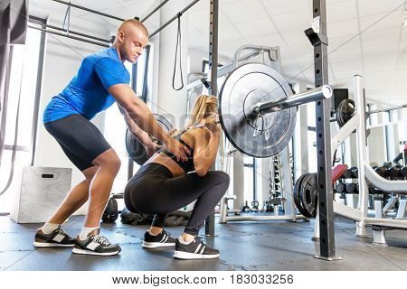 Personal trainer working with a client at the gym. Weightlifting workout assistance and motivation. Sport concept.