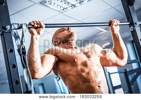 Muscular strong man training at a gym. chinup training. Bodybuilding and fatburning.