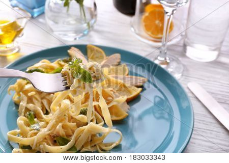 Fork with tasty pasta alfredo over plate on table