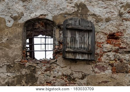 An old wall with sprinkled plaster. The window in the wall has an old wooden door. Riga. Latvia.