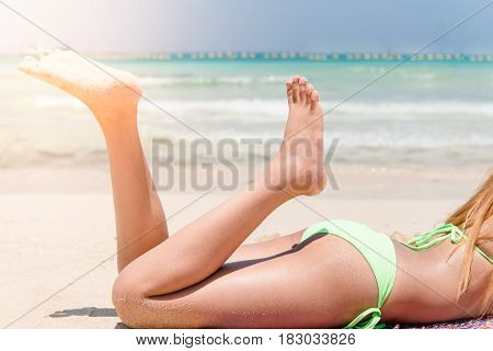 Sexy bikini body abs stomach closeup and tanned legs of beach woman relaxing tanning on beach on turquoise ocean or swimming pool at a tropical caribbean destination.
