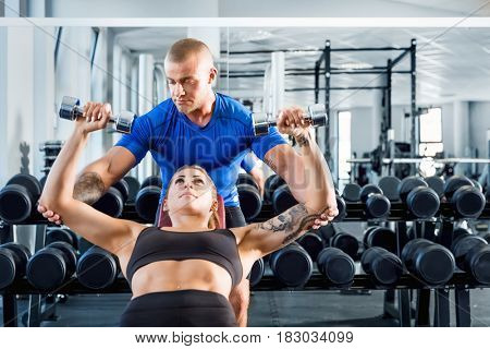 Personal trainer corrects and motivates while bodybuilding training at the gym. Professional help during workout. Healthy lifestyle and sport concept.