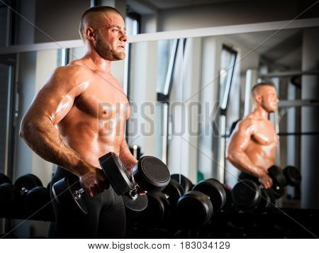 Muscular, strong man working out with dumbbells next to a mirror. Arm training and weight lifting in a gym. Sport and bodybuilding concept.