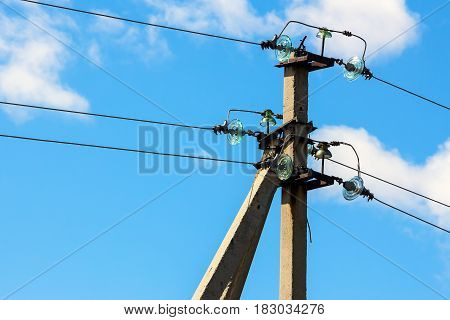Pillar with power line on background of blue cloudy sky