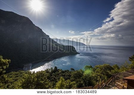 sun shining above mountains with blue sea in bay of mediterranean sea
