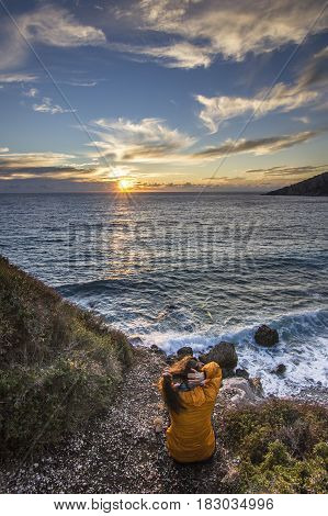 girl with long hair in yellow jacket sitting near seashore at colorful sunset of mediterranean sea