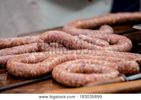 Butcher making tasty sausages in meat factory.