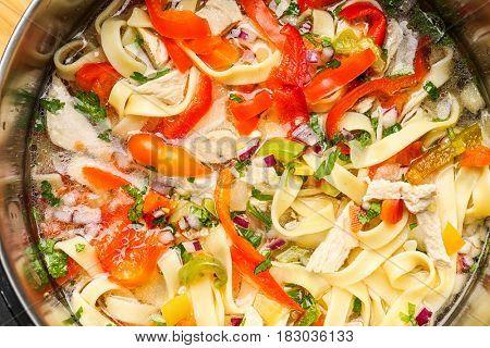 Chicken noodle soup in saucepan, closeup