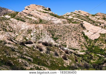 Sandstone rock formations being uplifted from the San Andreas Fault surrounded by green grasslands taken the Mormon Rocks in Cajon, CA
