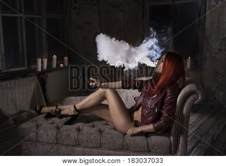 Young sexy redhead woman sitting on sofa and smoking , vaping e-cigarette.A cloud of vapor.Studio shooting.
