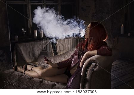 portrait of sexy redhead  woman on the sofa vaping e-cigarette , vape mod concept