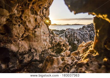 view from hole in stone on volcanic beach on Mediterranean Sea surrounded by mountains