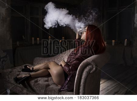sexy redhead woman on the sofa smoking electronic cigarette, vape mod concept