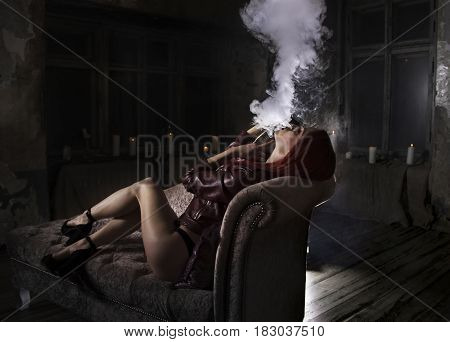 sexy redhead woman smoking electronic cigarette and lying on the sofa, vape mod concept