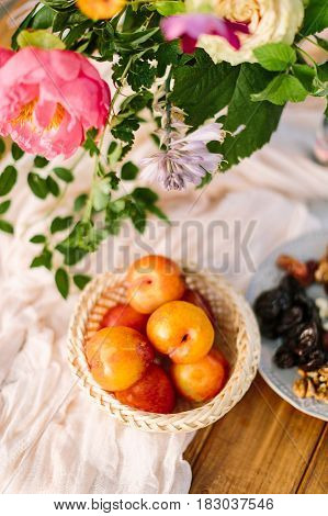 picnic, food, summer, holiday concept - close-up on the festively decorated table with beautiful pink peony and white rose flowers, fresh and dried fruits, nectarines, walnuts, prunes, tableware
