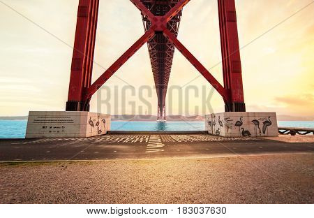 LISBON PORTUGAL - October 21 2016: Sunset over the 25 de Abril bridge over Tagus river and Christ monument in Lisbon Portugal