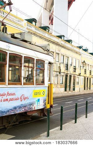 LISBON PORTUGAL - October 29 2016: The Ponte 25 de Abril Bridge and famous yellow tram on the street in Lisbon Portugal