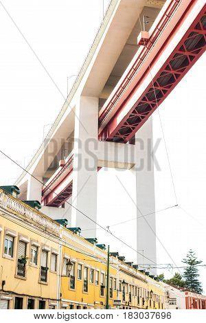 LISBON PORTUGAL - October 29 2016: The 25 de Abril bridge over city buildings or residential quarter in Lisbon Portugal. Living under the bridge