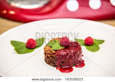A chocolate cupcake with chocolate frosting served with fresh ripe raspberry.