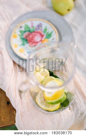 picnic, food, summer, holiday concept - glass decanter with ingredients for lemonade, lemon slices, lime, mint leaves, beside the table a festive clean dishes, a pear, selective focus