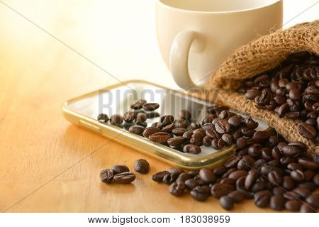 Coffee beans in the sack put on the smart phone with cofee cup on wooden table.
