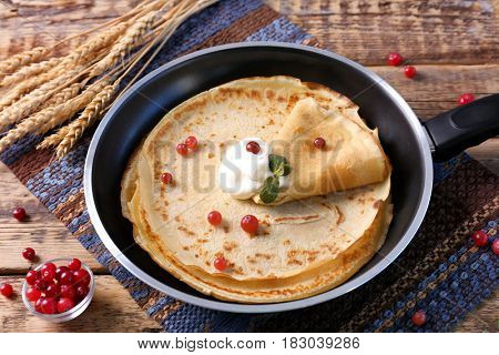 Pan with delicious pancakes and cranberry on table