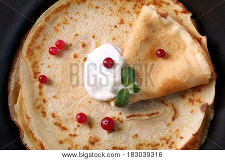 Pan with delicious pancakes and cranberry, closeup