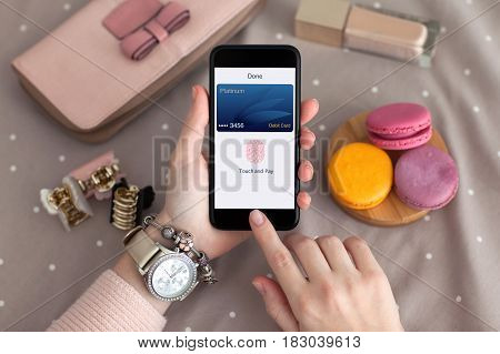 female hand jewelry holding phone with debit card app touch pay