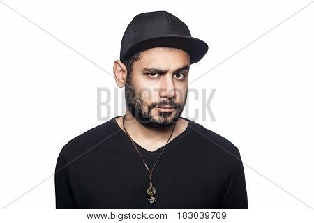 Portrait of young doubtful thinking man with black t-shirt and cap looking at camera with unsure eyes. studio shot isolated on white background.