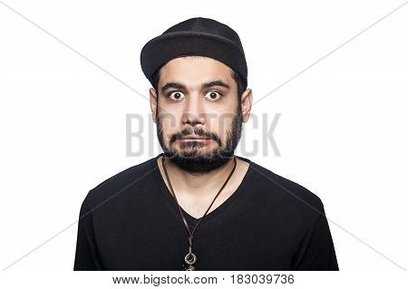 Portrait of young shocked surprised unhappy man with black t-shirt and cap looking at camera. studio shot isolated on white background.