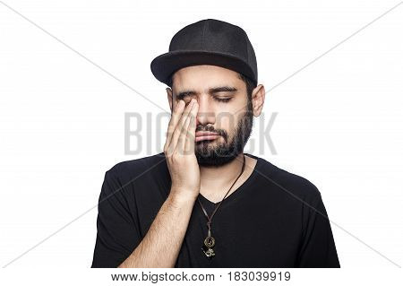 Portrait of young unhappy sad man with black t-shirt and cap looking at camera crying closed eyes. studio shot isolated on white background.