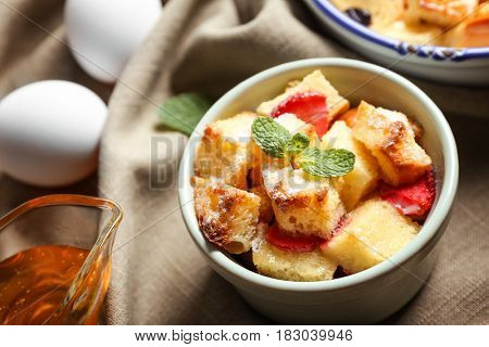 Delicious bread pudding with strawberry in bowl on napkin