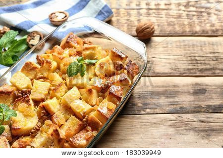 Delicious bread pudding with raisins in glass dish on wooden table