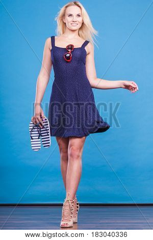 Summer trendy fashionable outfit ideas concept. Woman wearing short navy dress holding flip flops and sunglasses.