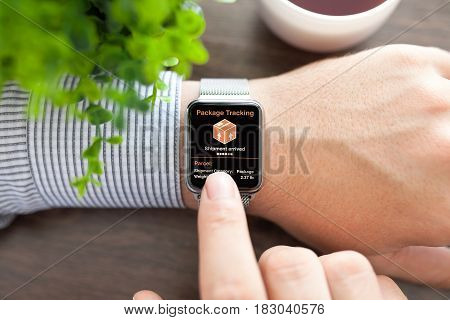 men hands smart touch watch with app tracking delivery package on screen